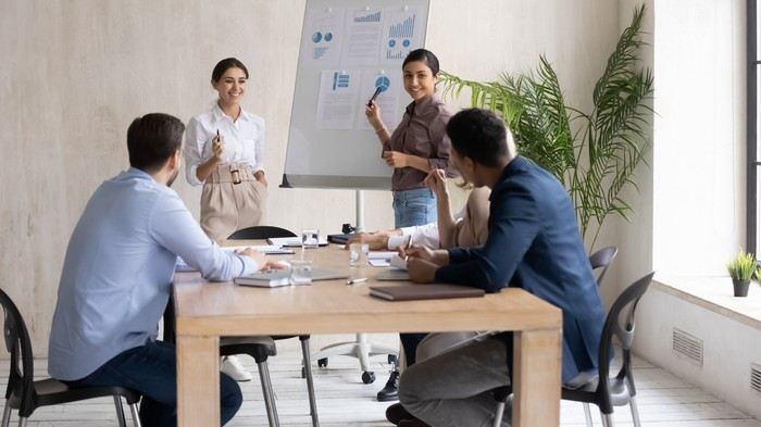 People in a meeting make a sales presentation.