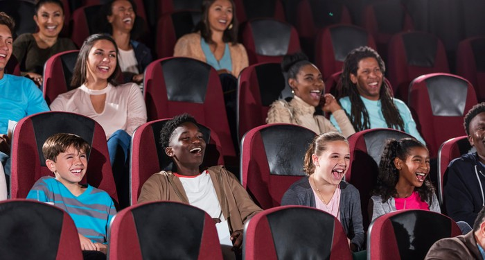 Smiling people sitting in a movie theater.