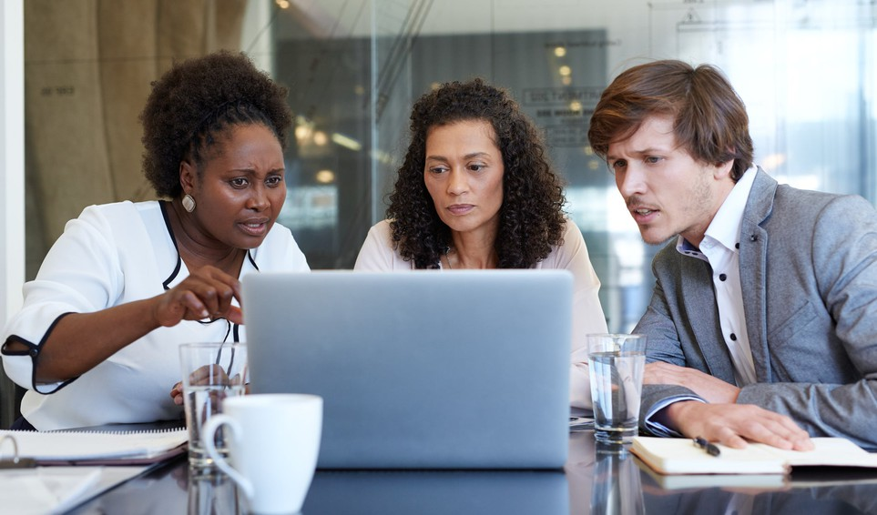 3 frowning people looking at a laptop