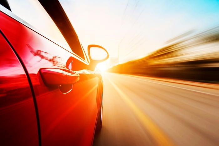 Car speeding along a highway near dawn or dusk.