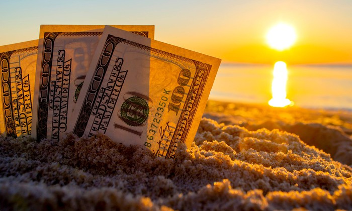 Three $100 bills stuck in sand on a beach with the sun rising over the water.