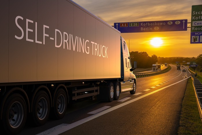 """Dark truck -- with """"self-driving truck"""" written on side of trailer -- traveling on a highway at sunset or sunrise."""