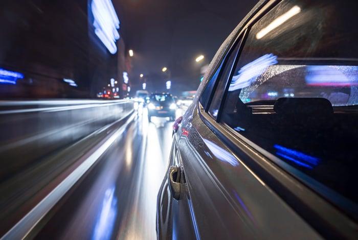 Cars driving along an urban road at night.