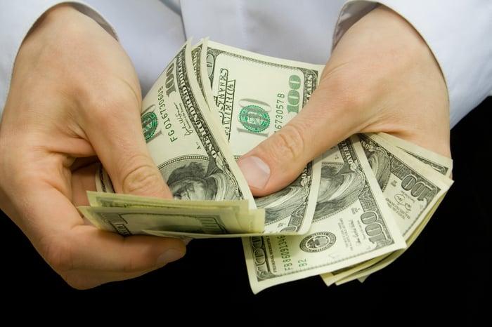 Une personne comptant une pile de billets de cent dollars dans ses mains.