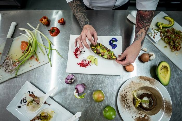 Un chef tatoué travaillant les fruits et légumes.