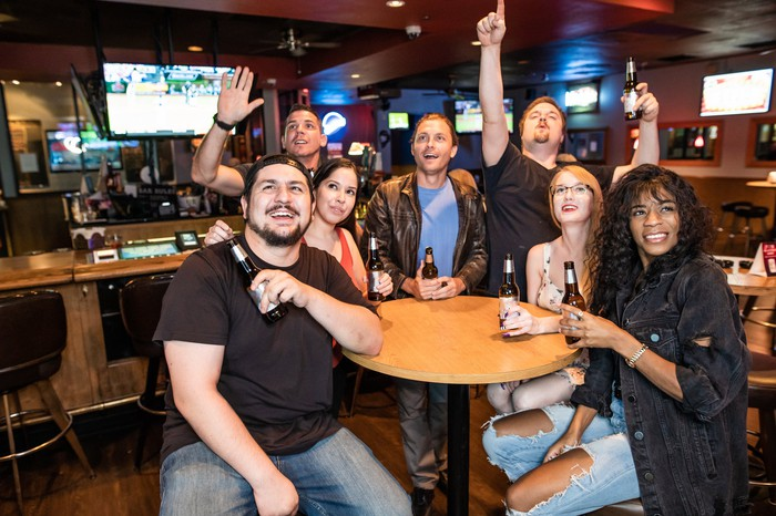 a group of people cheer while sitting around a table holding drinks in a sports bar