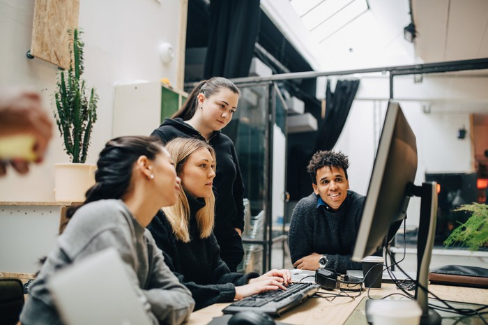 Four people work together in front of a computer.