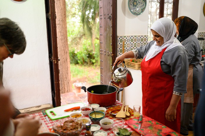 A local person pouring liquid into a pot in an Airbnb in Morocco.