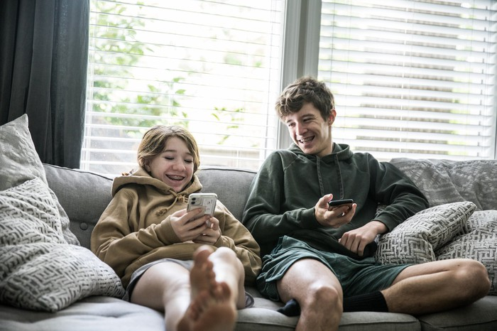 Two teenagers holding smartphones sitting on a couch.