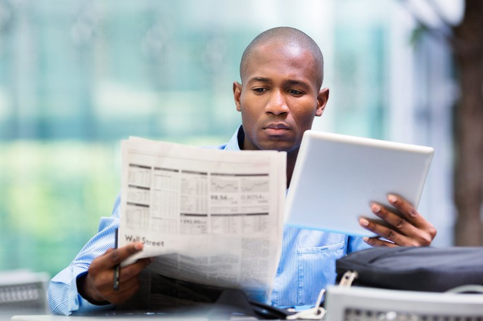 Person reading newspaper and other documents.