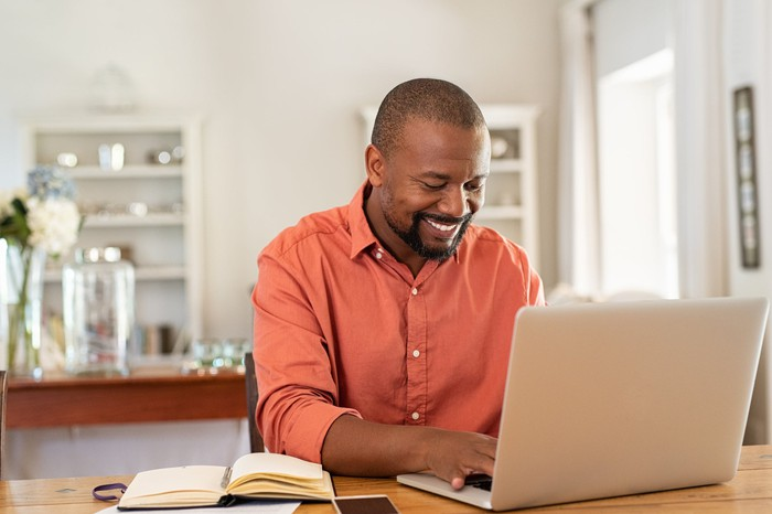 Smiling person typing on laptop.