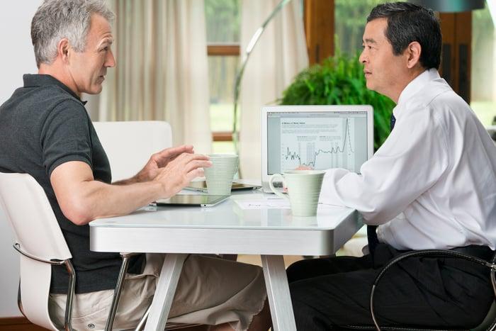 Deux personnes regardant un tableau financier sur un ordinateur portable.