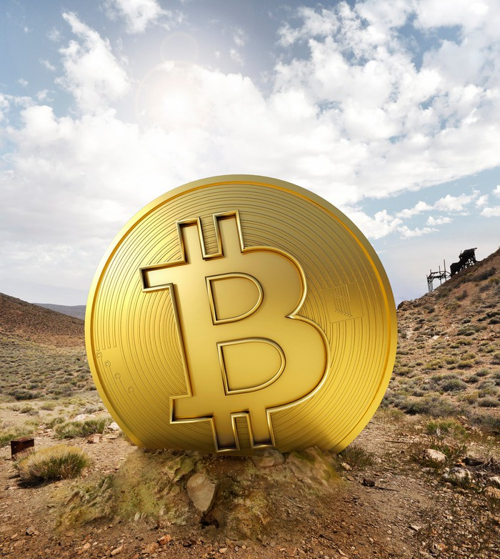 A huge gold coin with a bitcoin symbol in the middle of a desert.
