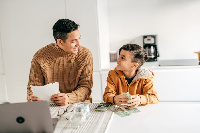 An adult holding papers and a child holding money sitting at table.