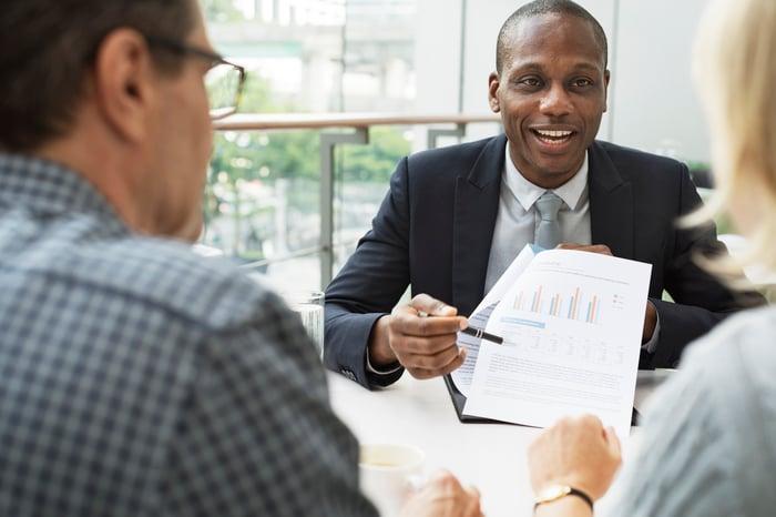 Three people sitting at a table looking at charts