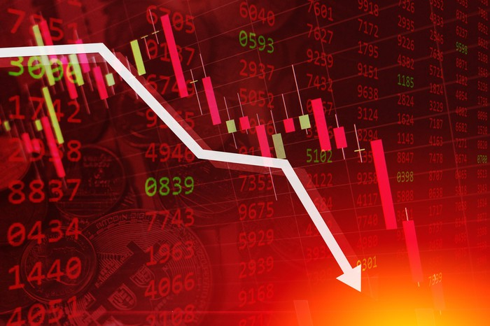 White arrow declining sharply atop a stock ticker tape display bathed in red.