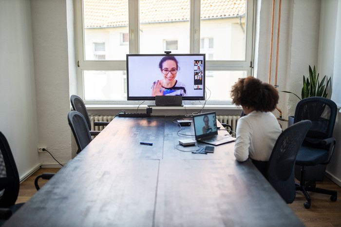 Une personne dans un bureau discutant par vidéo avec plusieurs autres personnes.