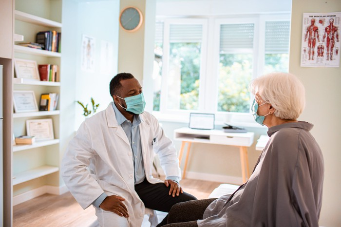 Elderly patient conferring with a doctor, as both men are face-masked.
