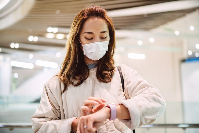 Woman in face mask using a smartwatch.