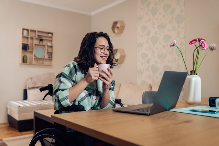 A person in a wheelchair drinking coffee while smiling at a laptop.
