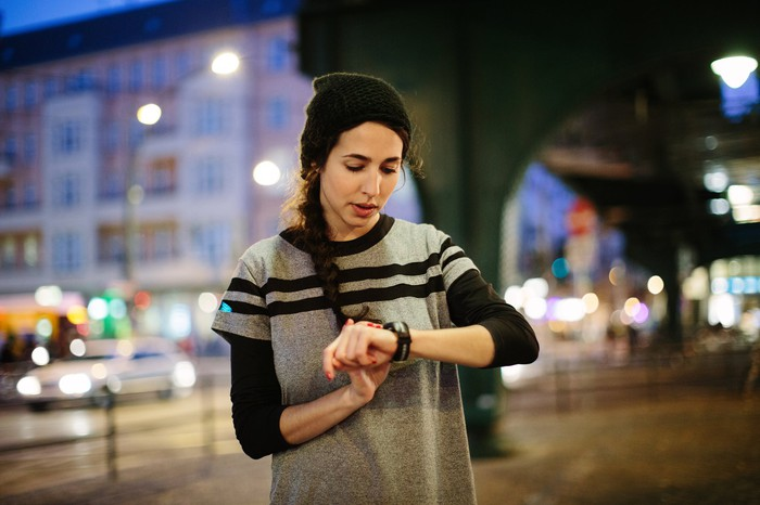 A young woman checks a smartwatch in a city at night.