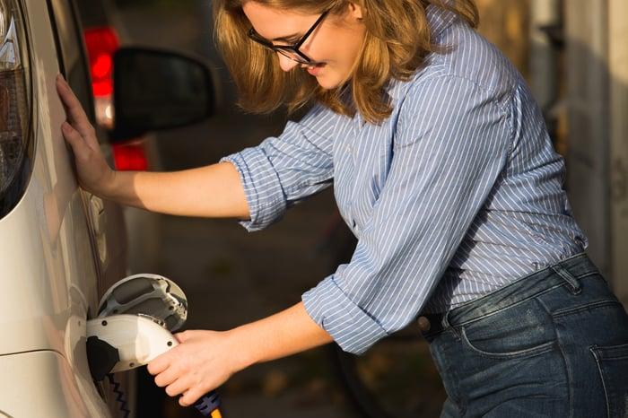 Woman charging an electric car.