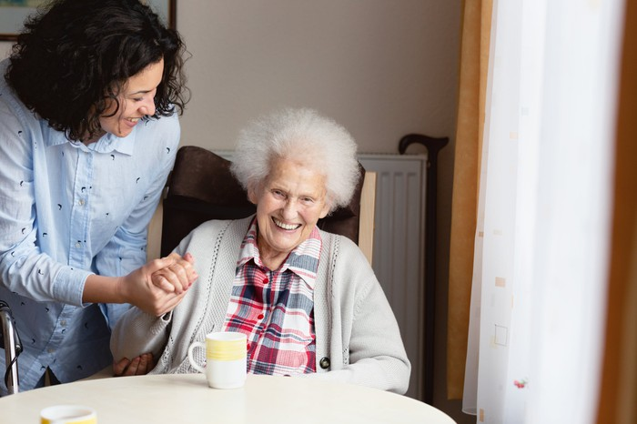 An older person seated and smiling being cared for by another person standing alongside.