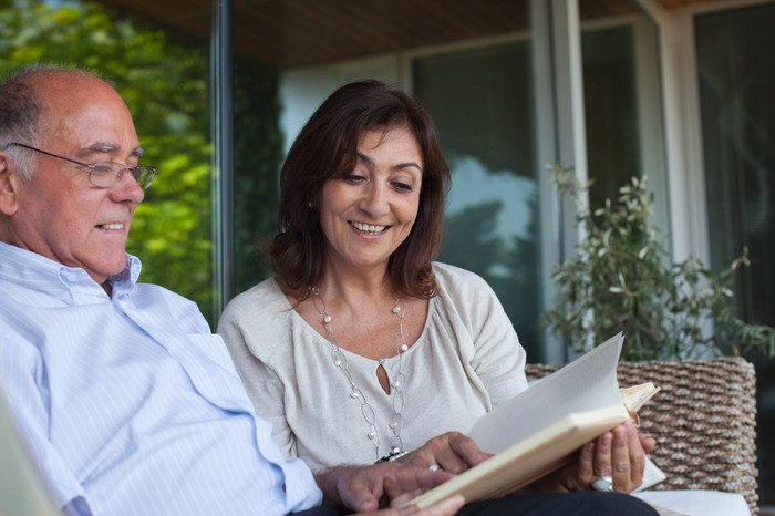Two people looking at book outdoors