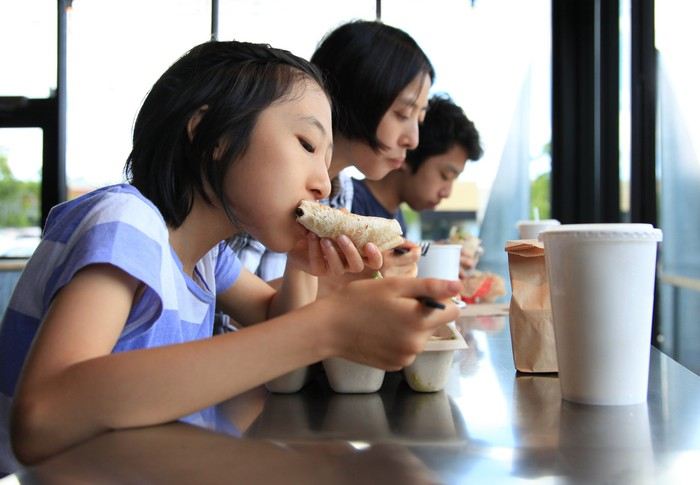 A family of three eats together at the counter of a restaurant