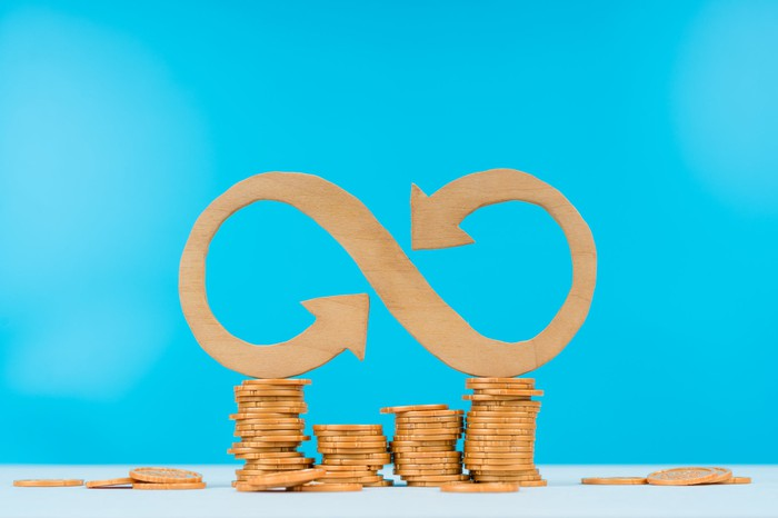Wooden infinity sign on top of wooden coins.