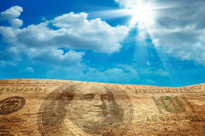 A one hundred dollar bill image superimposed on sand, with the sun breaking through the clouds.