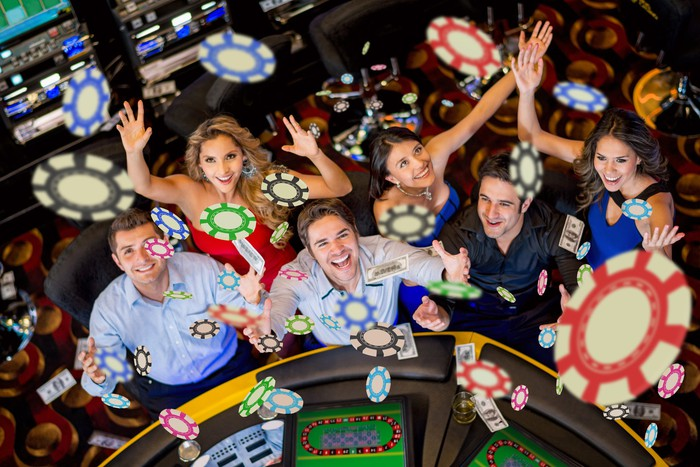 A group of people throwing chips in the air at a casino.
