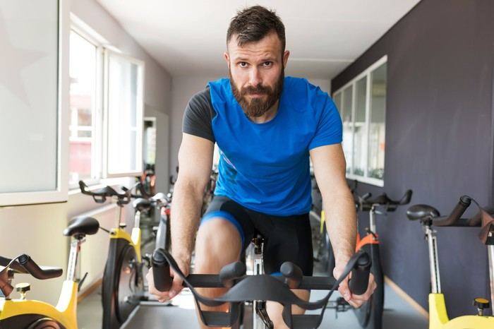 A man in workout clothes riding a stationary bike.