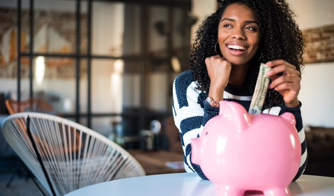 Young woman smiling while putting a dollar bill into a piggy bank
