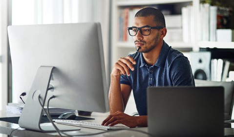 investor sitting at computer with pen