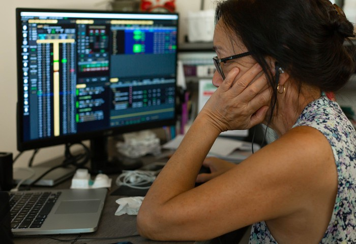 An older person looking at stock charts on their computer monitor.