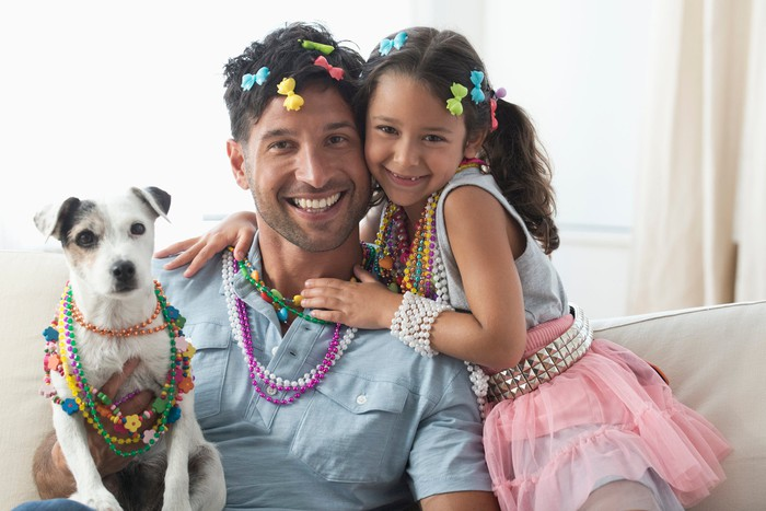 A dad with his daughter and pet dog. They are all wearing bows in their hair and smiling.