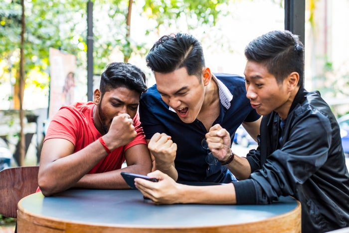 A group of friends huddled around an outdoor table while playing a mobile game.