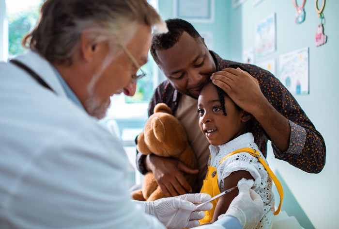 Child receiving a vaccine shot while being comforted by an adult.