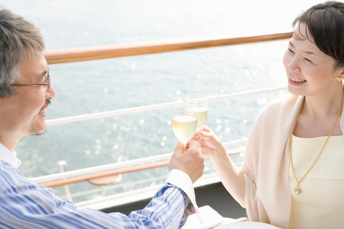 A couple clinks wine glasses together as they sail on a cruise ship.