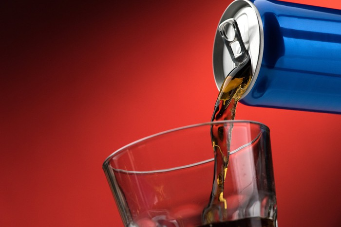 A soft drink being poured into a glass from a blue aluminum can, against a red background.