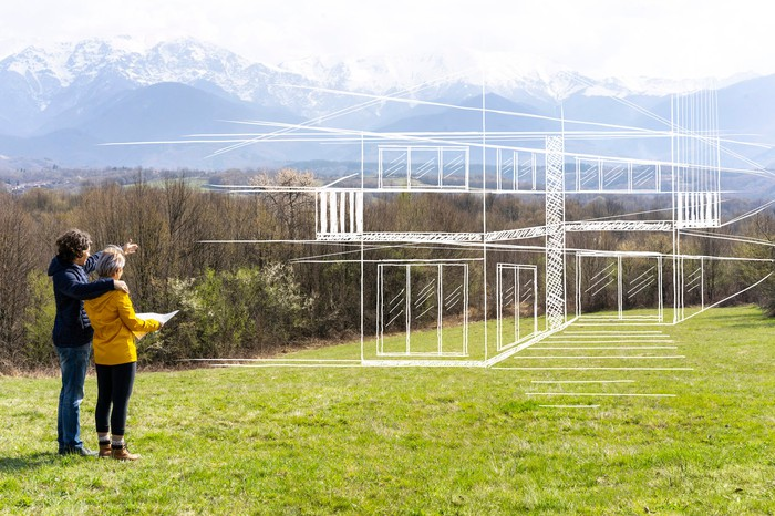 Two people look out over an empty lot in the mountains, imagining a home built to their specifications.