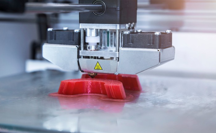 Close-up of a silver 3D printer head printing a red plastic object.