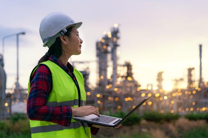 Une personne portant un casque de sécurité tient un ordinateur portable près d'une raffinerie.