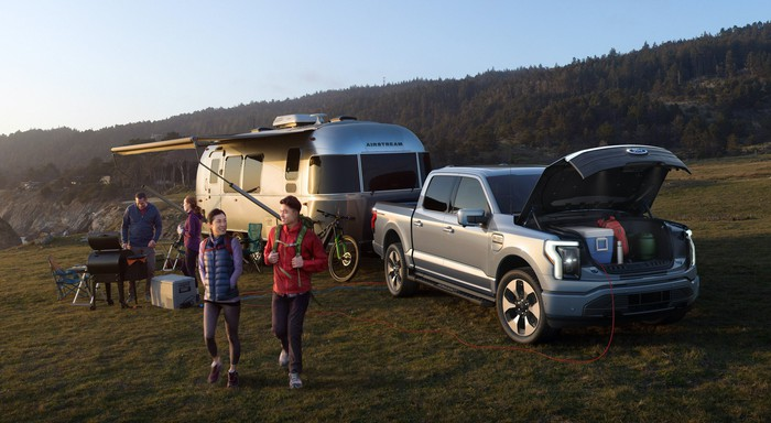 A silver Ford F-150 Lightning, an electric pickup truck, with an Airstream camping trailer at a campsite.