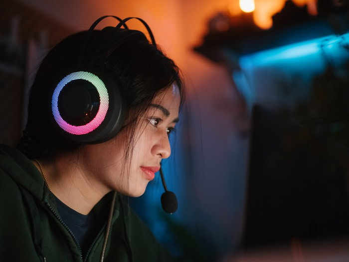 A gamer wearing a headset with a microphone while playing a game on a PC.