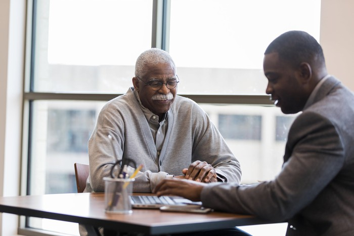 An older gentleman is consulting with a younger man, possibly a financial adviser.