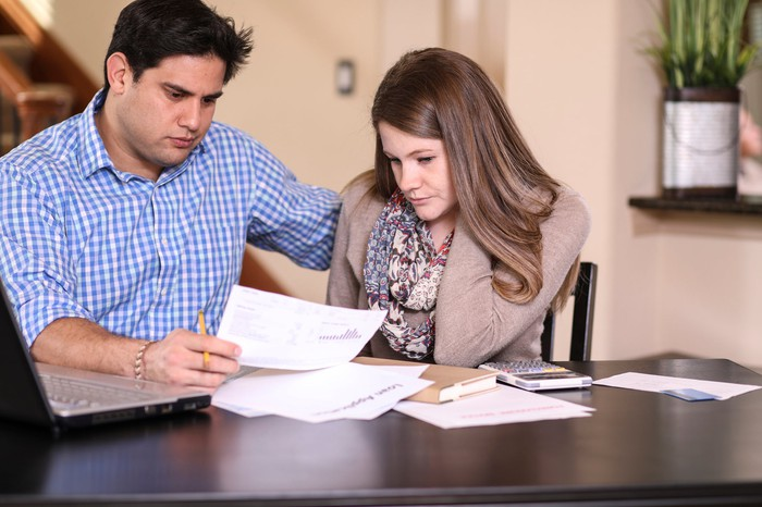 A young couple, looking over their finances, concerned.