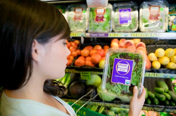 A shopper picks out organic lettuce.
