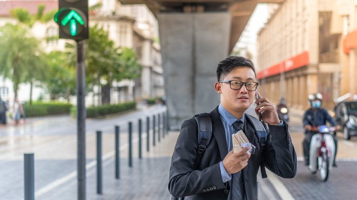 A young businessperson standing on a median, holding a sandwich and smartphone, and seemingly waiting for a ride.